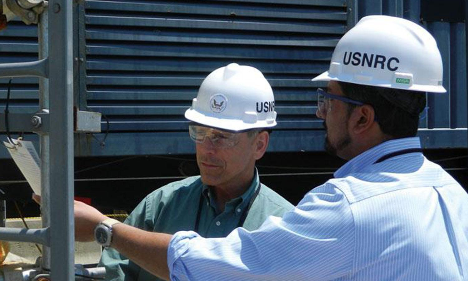 Two men with white USNRC hard hats look at document
