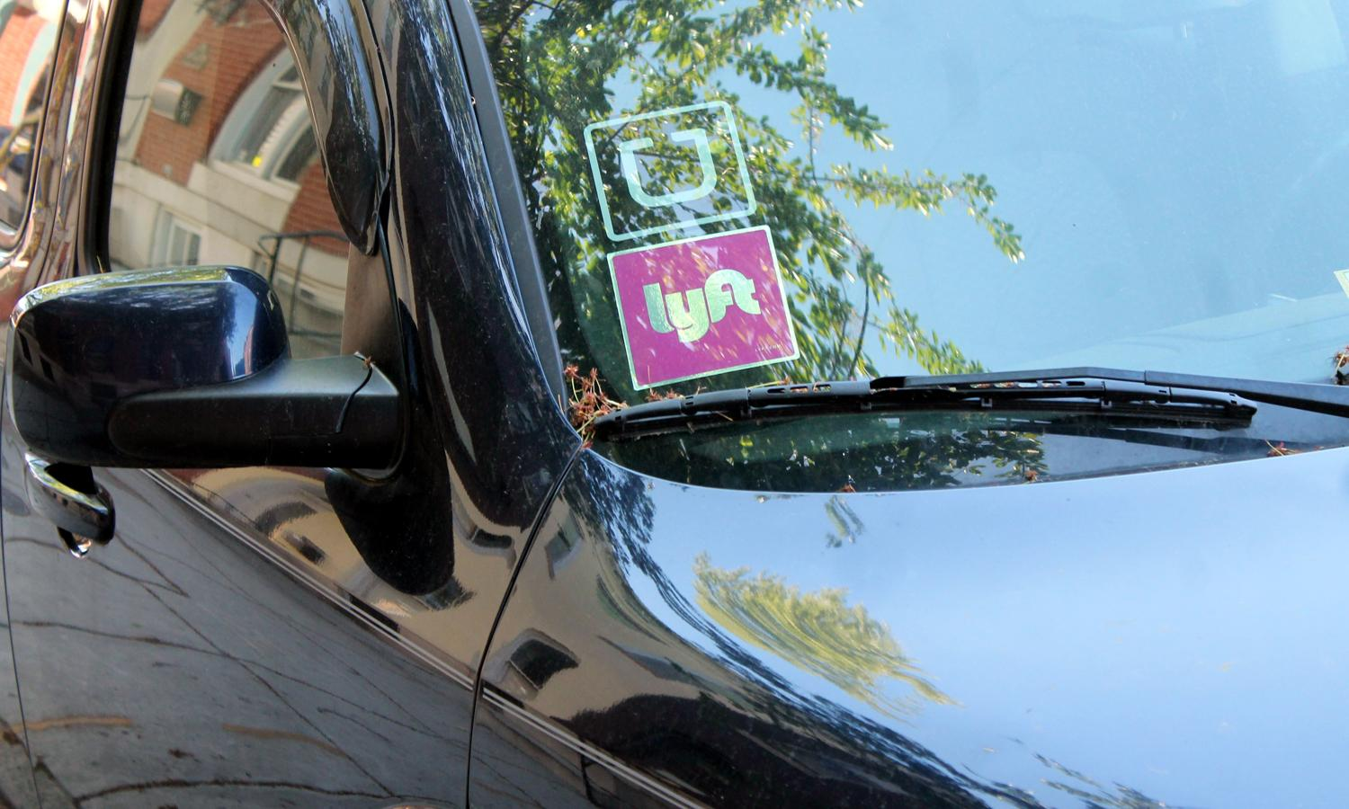 Uber and Lyft stickers in a car window
