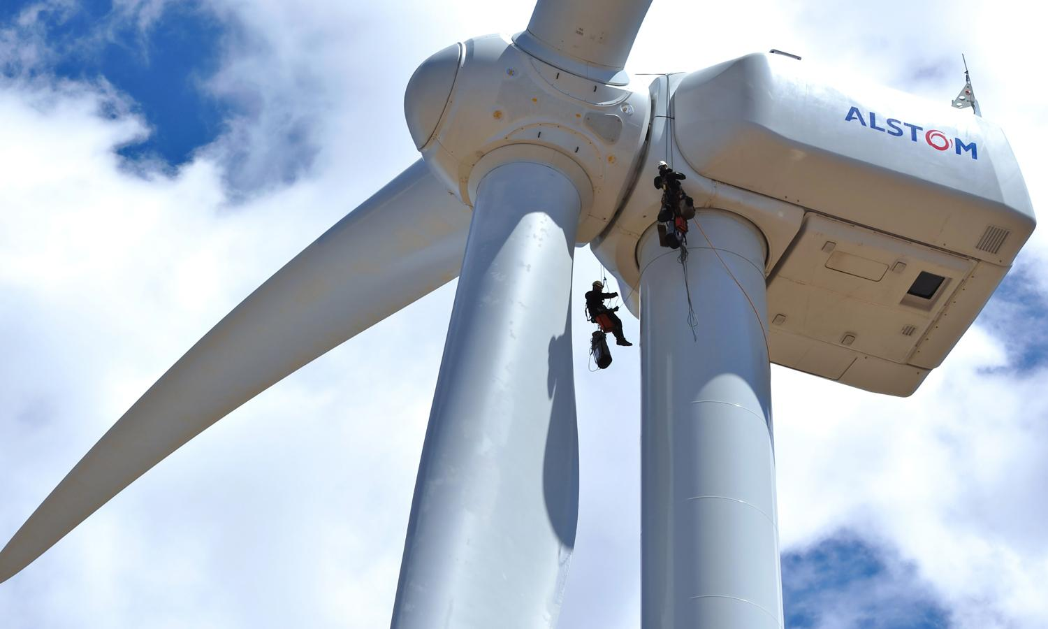 Two workers on the top of a wind turbine.