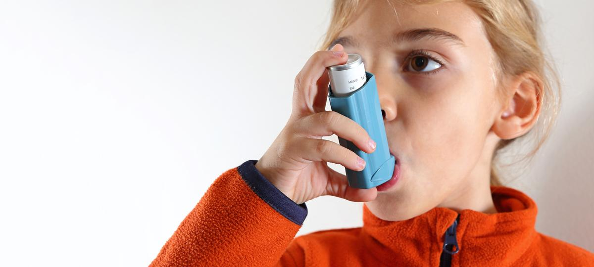 girl using asthma inhaler