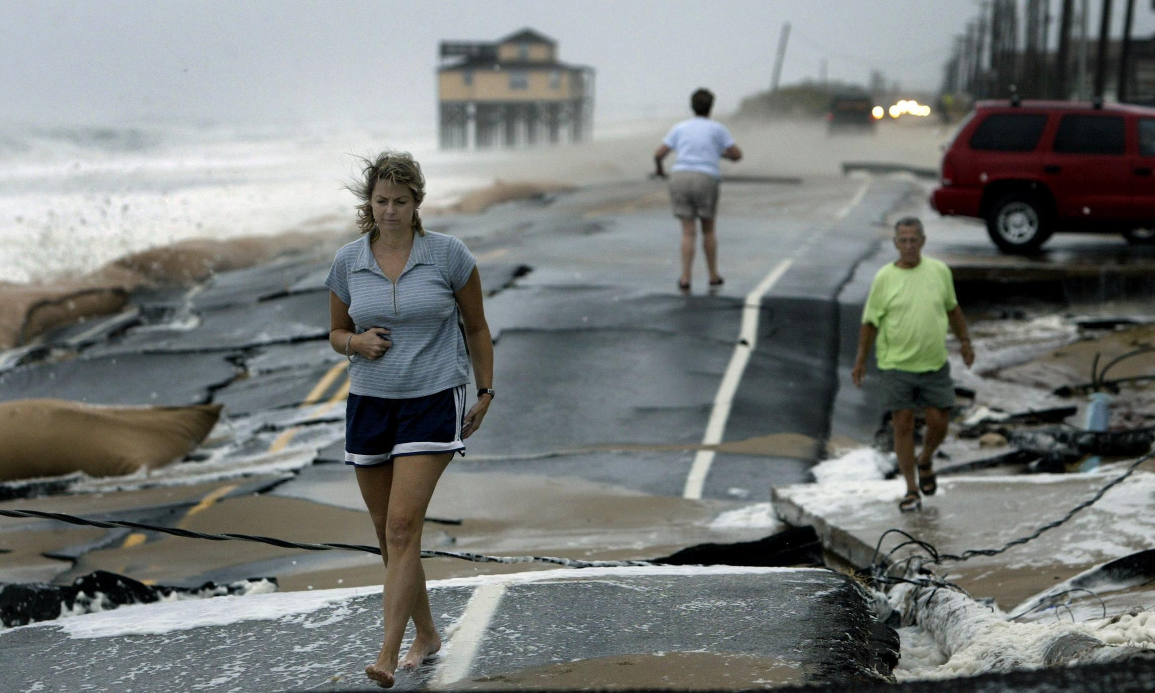 Three people walk on a road that's been broken apart by a storm.