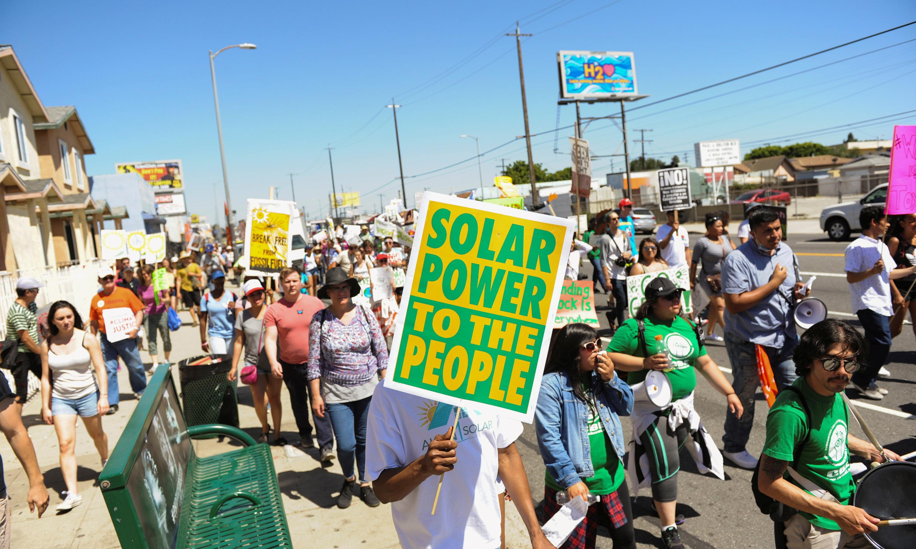 "A group of people marching with a sign that reads ""Solar power to the people."""