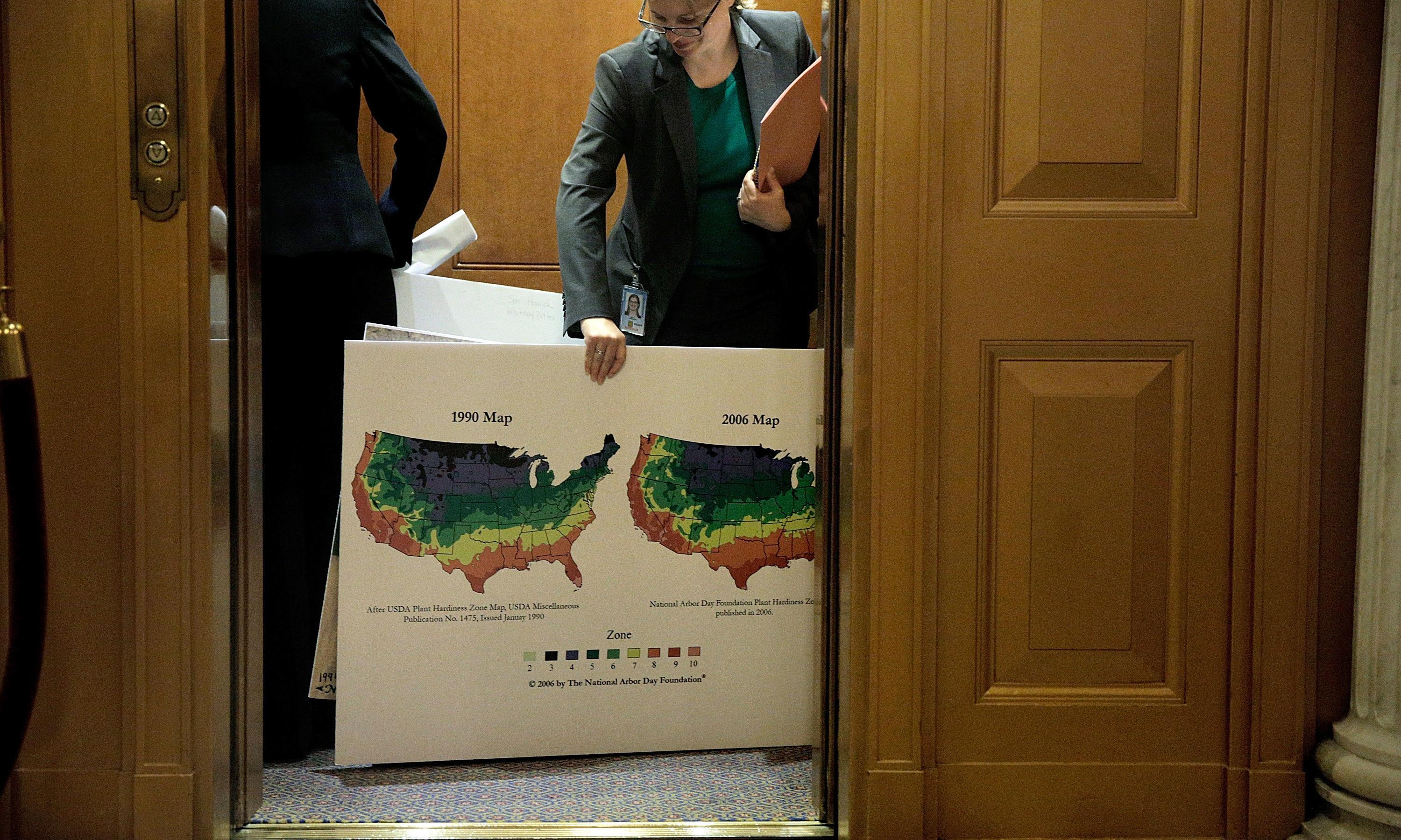 A woman entering a hearing holding a sign that shows two maps that compare plant hardiness zones.