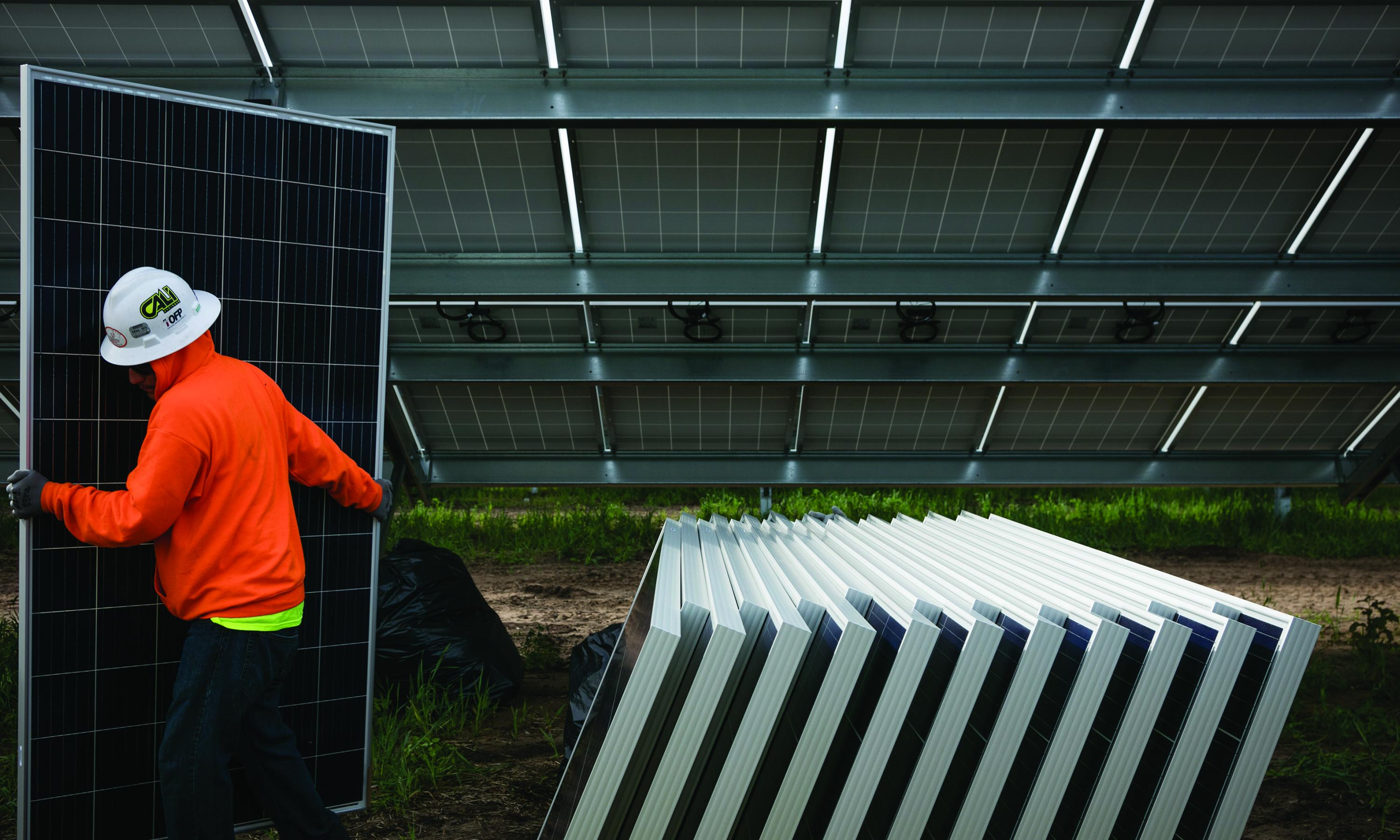 A worker carries a solar panel