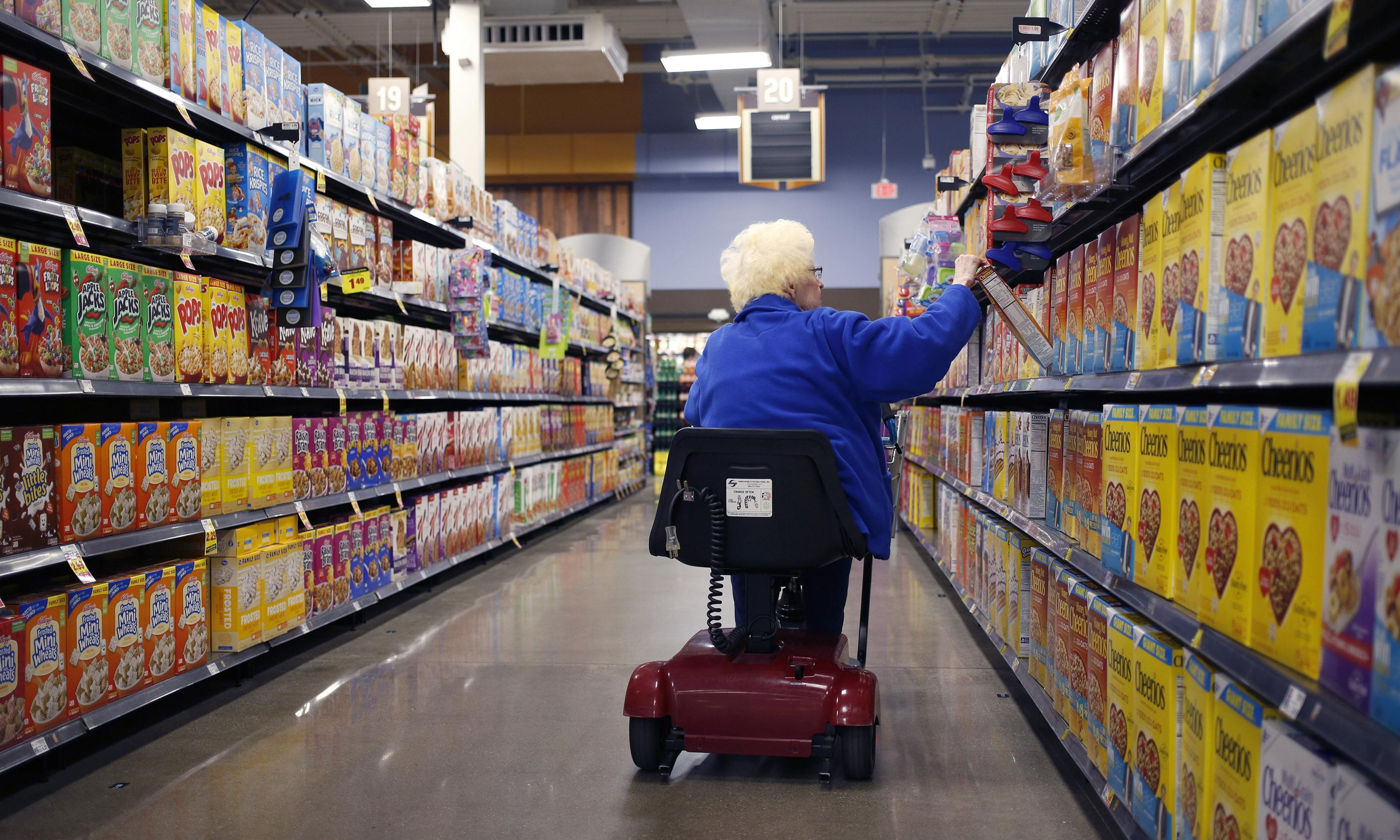 An older woman in a scooter goes down the cereal aisle of a supermarket