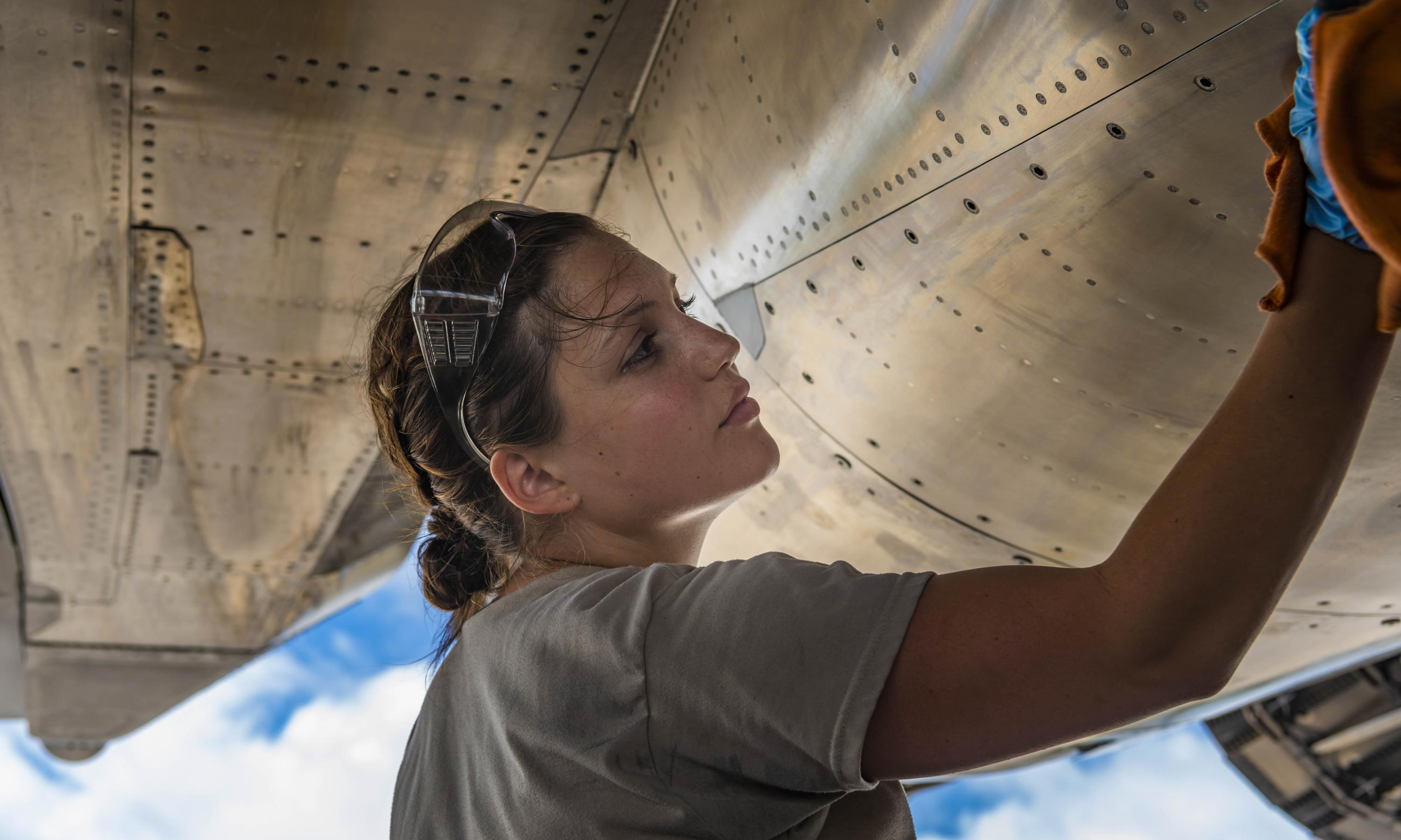 Airman cleans an aircraft during preflight inspections.