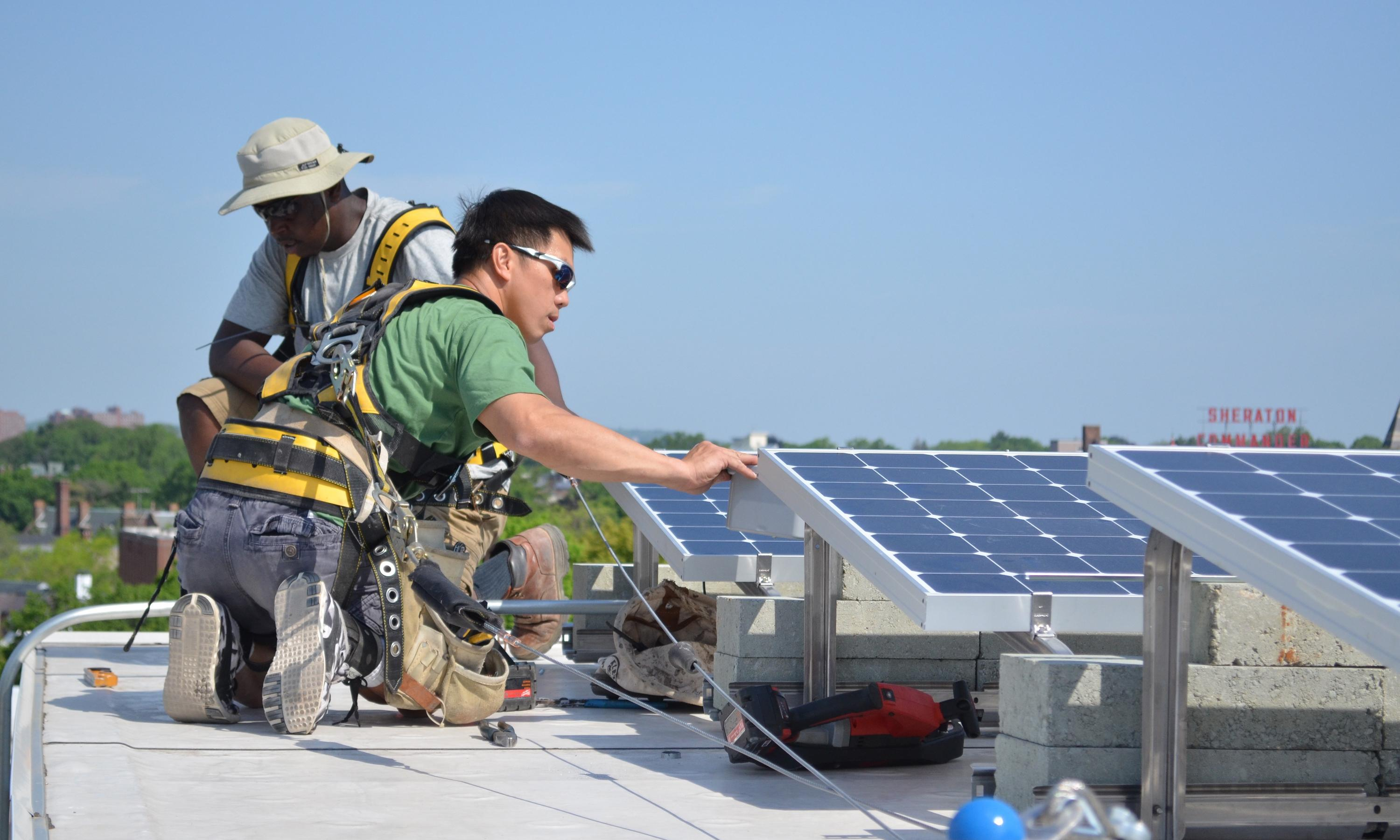 Two workers install solar panels on a roof