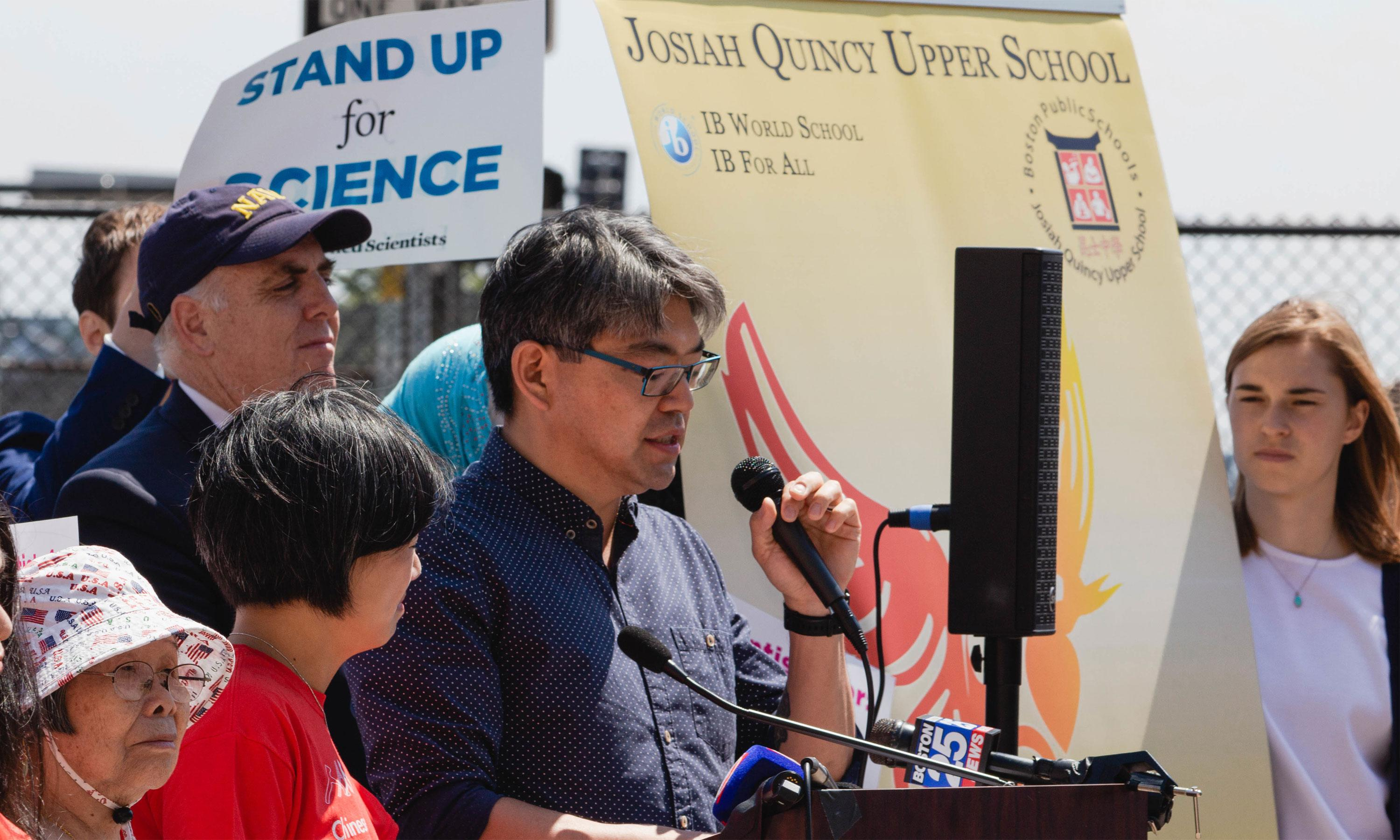 speaking at the mic with stand up for science behind