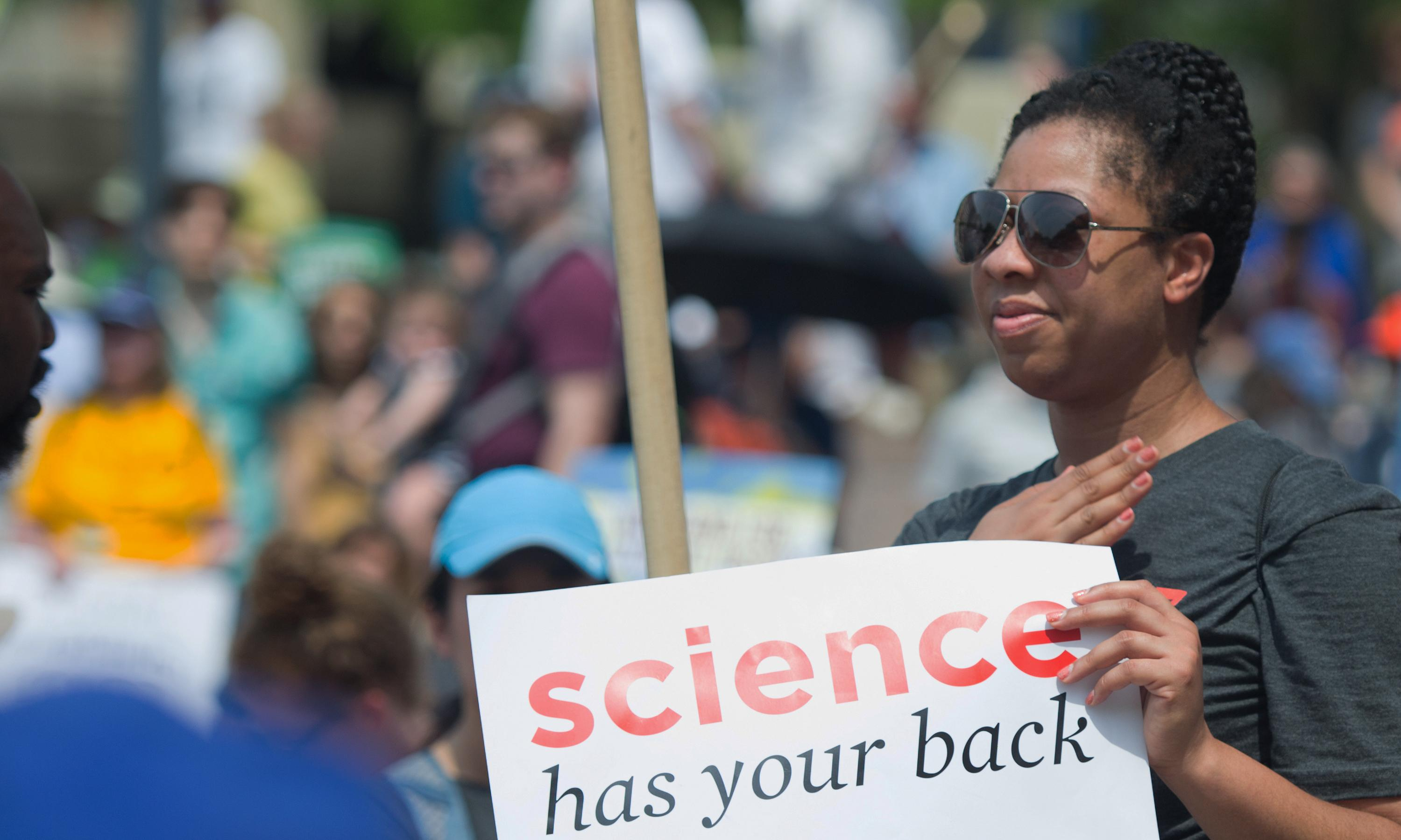 "Person holding a sign that reads ""Science has your back."""