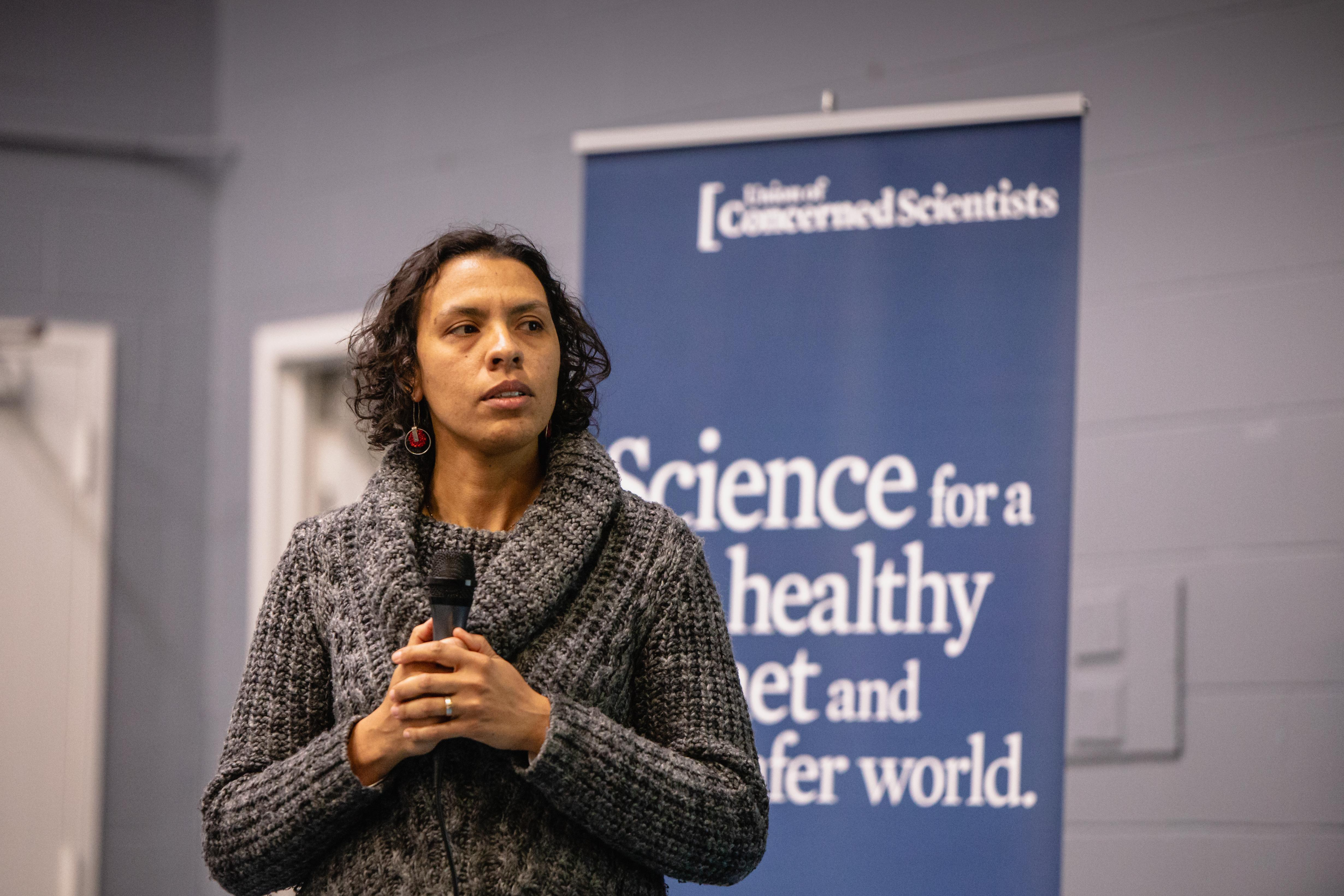 "A scientist standing in from of a sign that reads ""Science for a healthy planet and safer world"" holds a microphone"