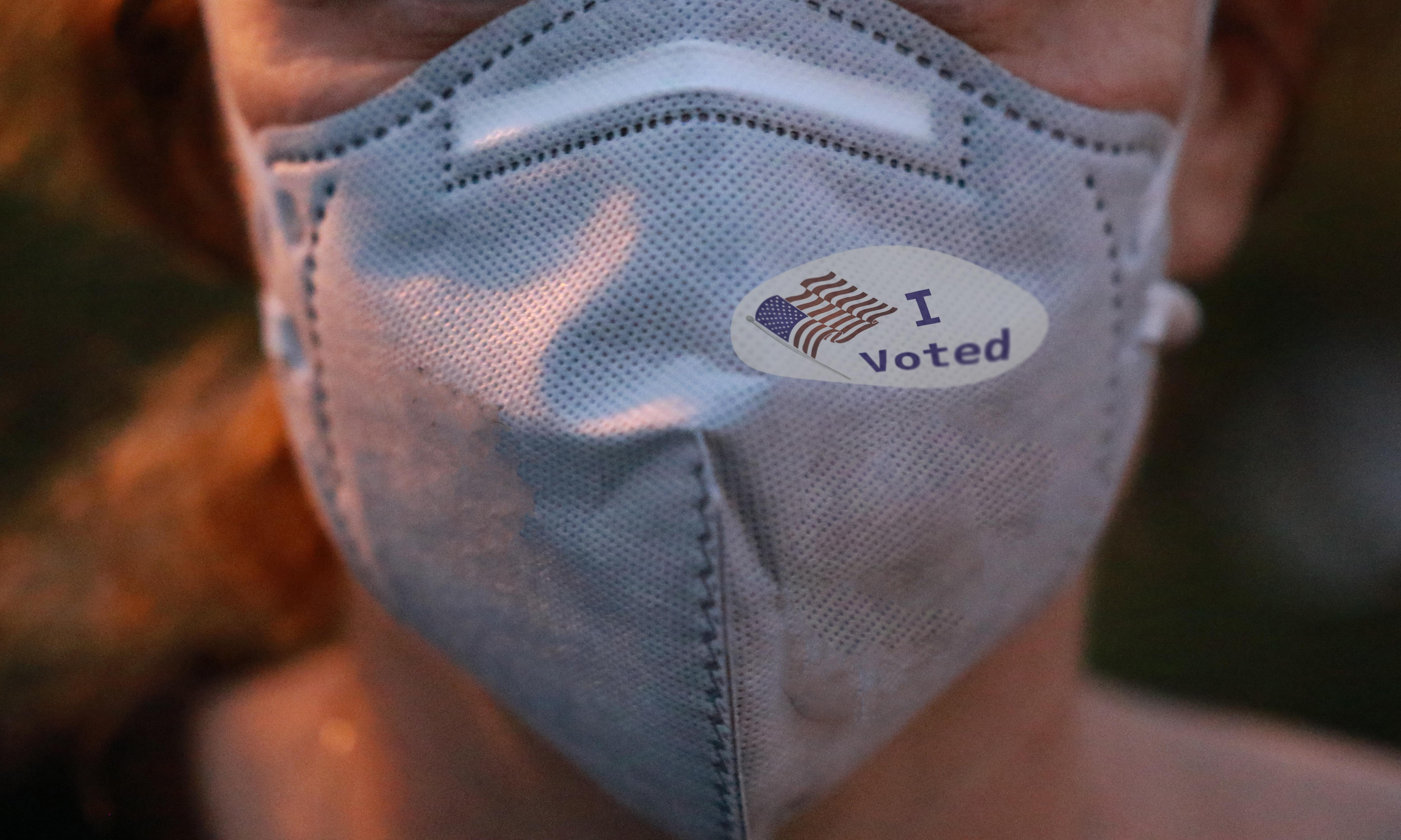 A person wearing a mask and a vote sticker