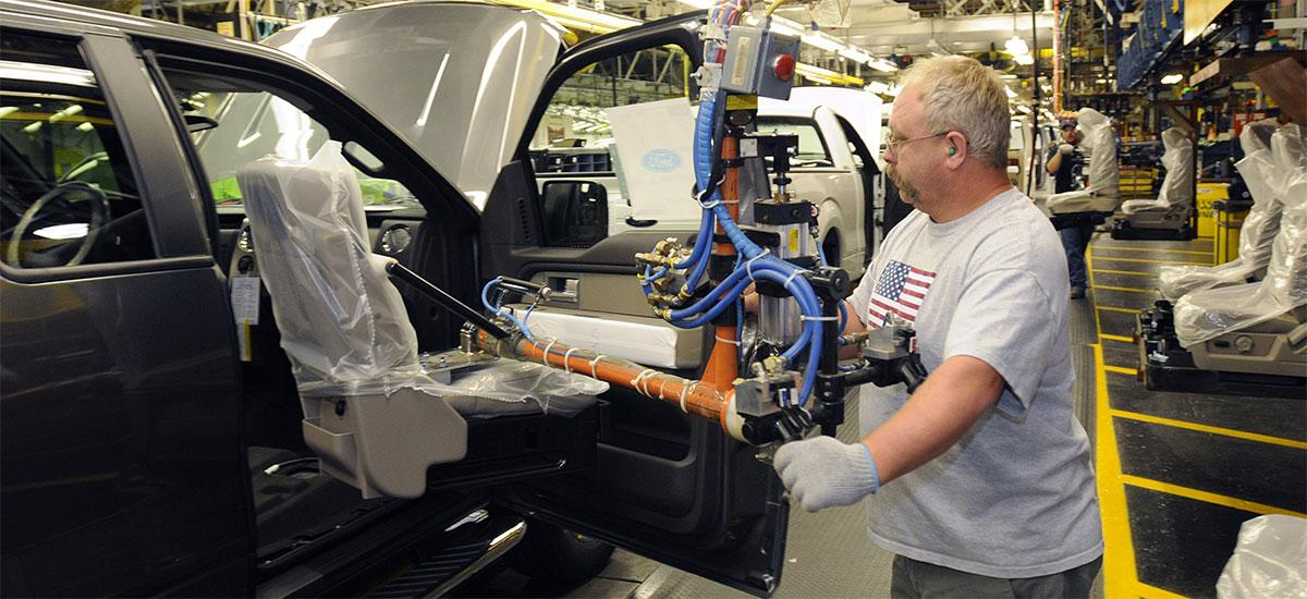 Auto worker installing car seat