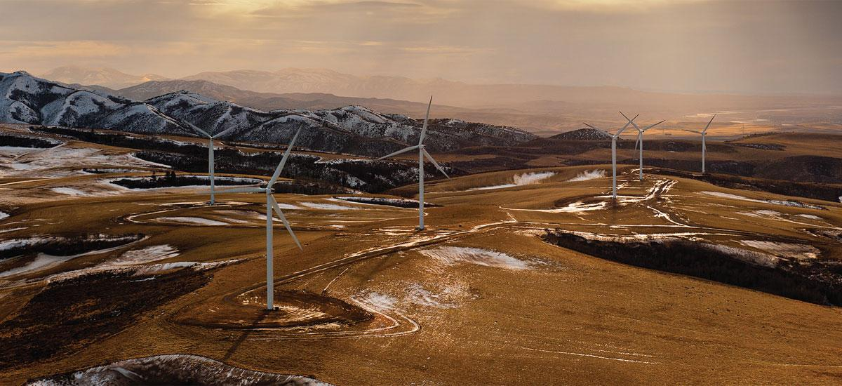 wind turbines on top of snowy desert mountains