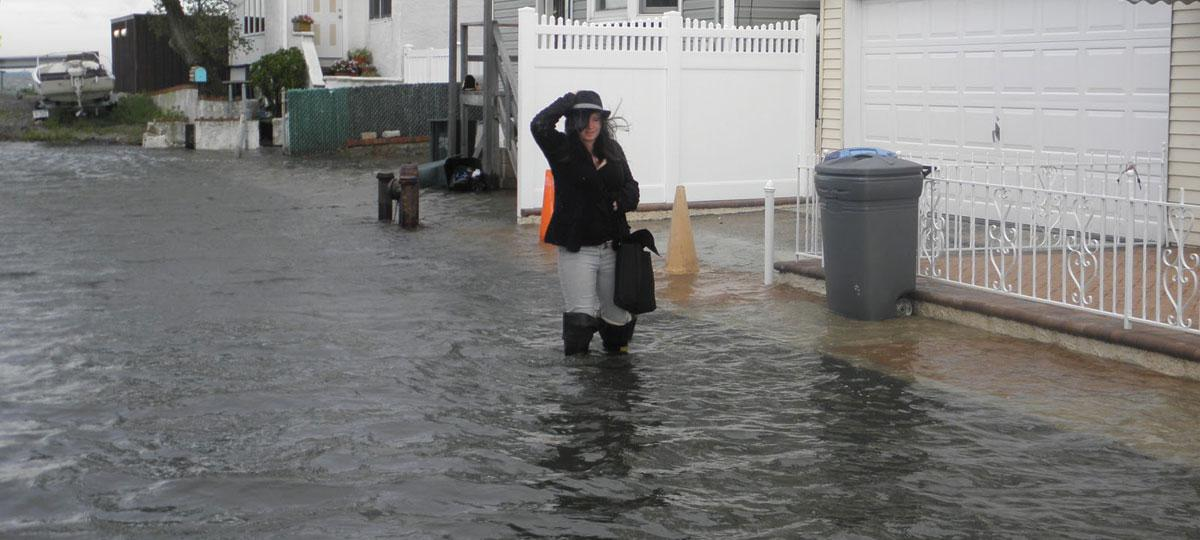 Girl wading through tidally flooded street in Jamaica Bay, New York