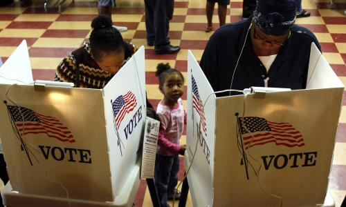 Two adults and a child stand in front of a voting booth