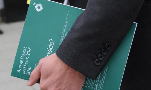 Person holding a BP annual report booklet.