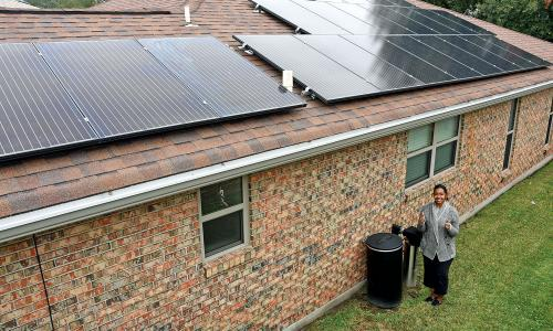 Woman giving thumbs-up beside house with solar panels on roof
