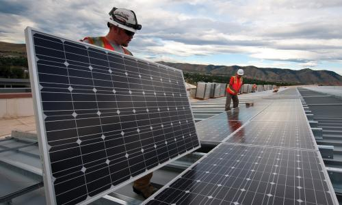 Two workers with hardhats installing rooftop solar panels