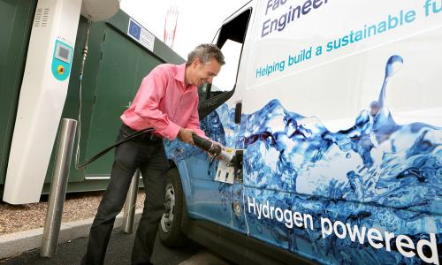 Man recharging hydrogen fuel cell vehicle