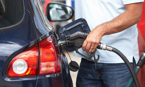 Man in white t-shirt pumping gas into blue car