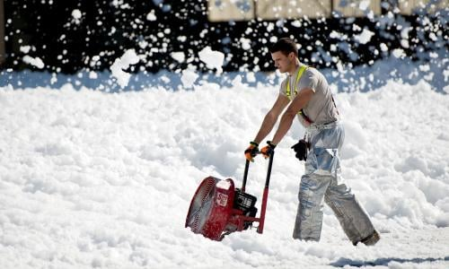 Worker using blower on firefighting foam