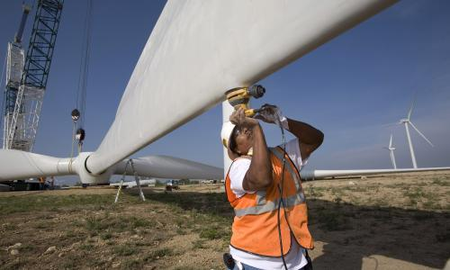 Worker helping to construct wind turbine blades.