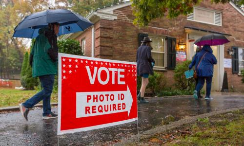 Voters walking to polling place in the rain, with sign saying photo ID required