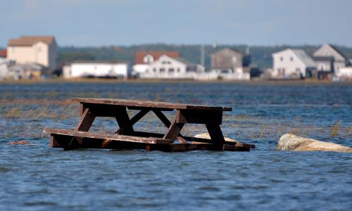 Flooded picnic table with houses in background in Seabrook, NH