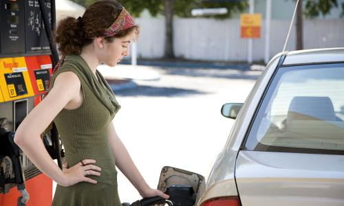 Young woman pumping gas