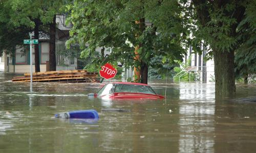 A red sedan is mostly submerged in flood waters in Cedar Rapids, IA.