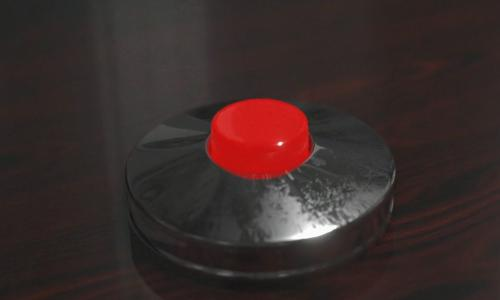 Red nuclear launch button on a wooden desk