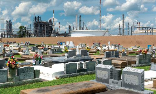 Cemetery in Cancer Alley, Louisiana, with refinery stacks in background