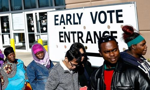 Voters stand outside an early voting poll entrance