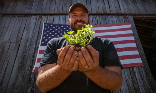 Farmer holding small plant in ball of soil in front of US flag