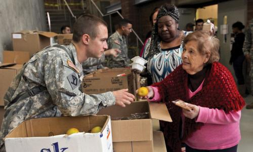 National guard soldier handing out fruit after Hurricane Sandy