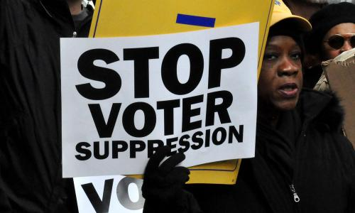 Woman holding 'Stop Voter Suppression' sign at voting rights march