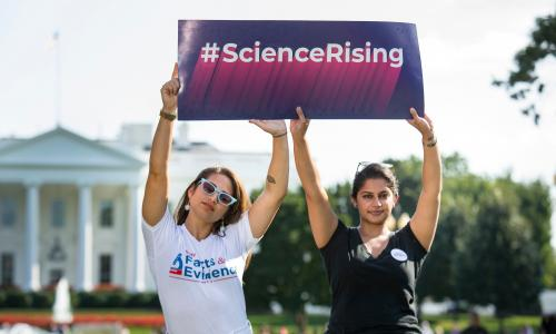 "Two women holding a sign that says ""Science Rising"""