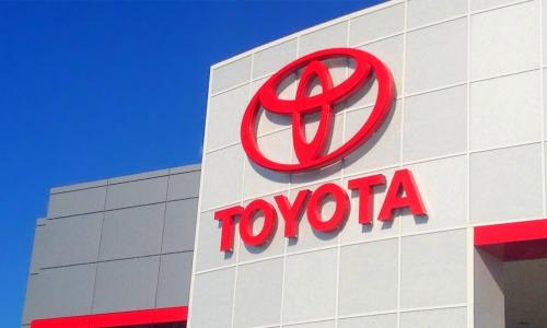 The red Toyota logo on exterior wall of one of its car dealerships