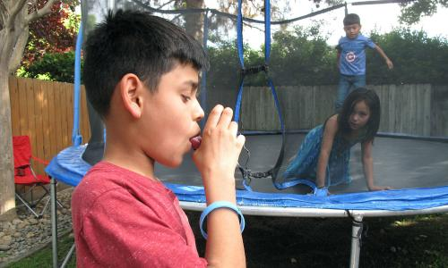 Boy using inhaler while playing with other kids