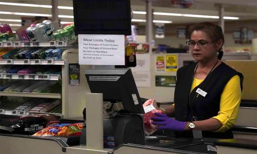 A cashier during the COVID-19 crisis, with food scarcity signs.