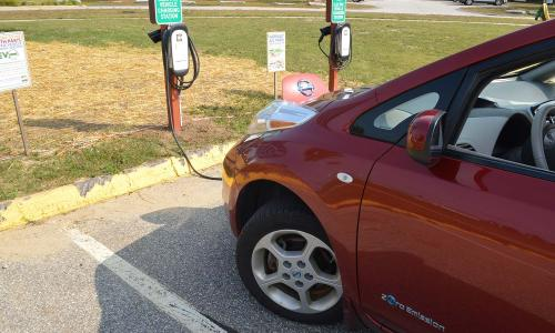 A red Nissan EV at a charging station in Maine