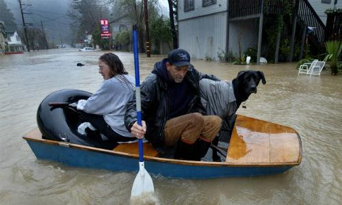 man woman dog rafting in flood waters caused by high flows on California's Russian River