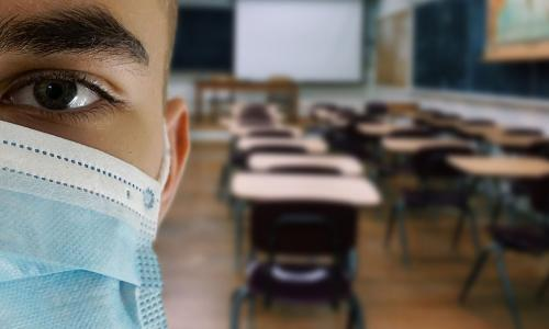 Student in an empty classroom wears a mask.