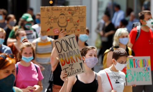 Climate change protester carries a sign that says 'Don't burn my future'