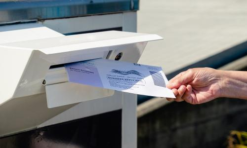 Voter depositing ballot in mailbox