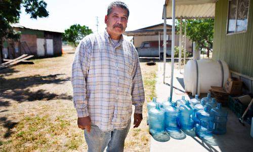 Male San Joaquin Valley community member stands in front of water jugs