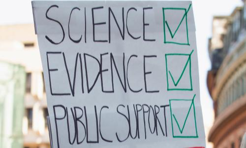 A sign that reads science, evidence, public support