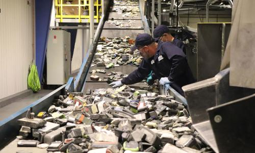 A conveyor belt sends lithium ion batteries to be shredded