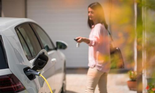 Woman using key fob to lock white electric vehicle that is charging