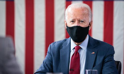 Photo of presidential candidate Joe Biden sitting with a mask on and a flag-like red and white background
